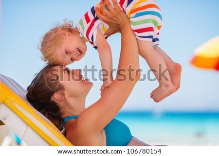 Happy mother playing with baby on sunbed