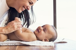 Happy mother playing with baby while changing his diaper. Smiling young woman with baby son on changing table at home. Close up of cheerful mom and toddler boy playing together.