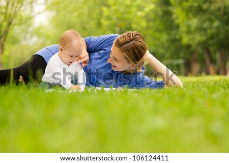 Happy mother playing with her baby in park