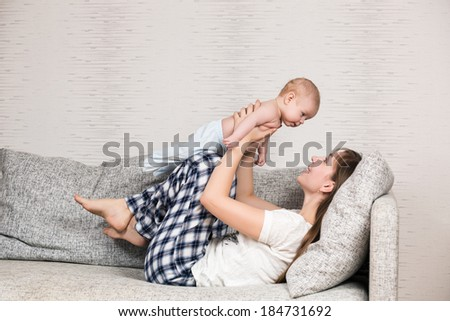 Happy mother playing with her cute loving baby at home
