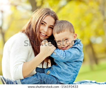happy mother playing with her son in the park