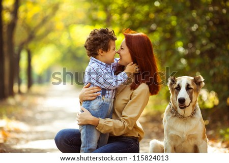 happy mother playing with her son in the park playing with the dog