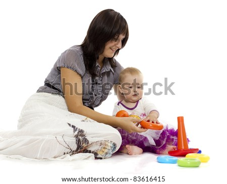 Happy mother plays with her baby sitting on a floor