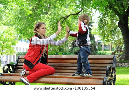 Happy mother plays with her child in park