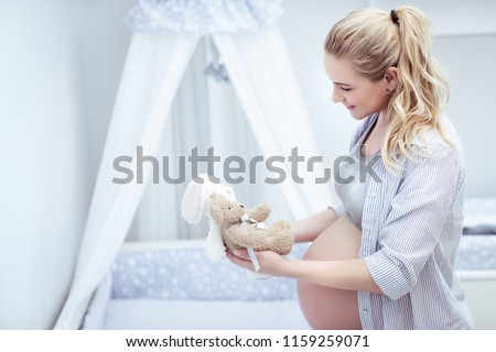 Happy mother prepares child's room, beautiful young pregnant woman with pleasure decorates bed of her future baby with toys, happy pregnancy concept