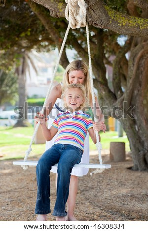 Happy mother pushing her daughter on a swing in a park
