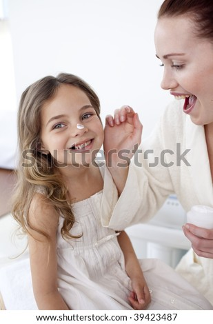 Happy mother putting cream on her daughter's face in bathroom