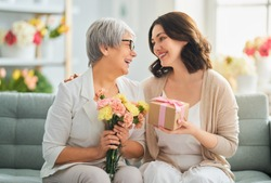 Happy mother's day! Beautiful young woman and her mother with flowers and gift box at home.