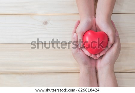 Happy Mother's day celebration and csr charity donation for nursing children family health care concept with mom parent or volunteer holds young kid's hands supporting red heart gift present