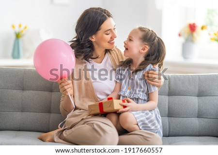 Happy mother's day! Child congratulating mom. Mum and daughter smiling and holding gift. Family holiday and togetherness.