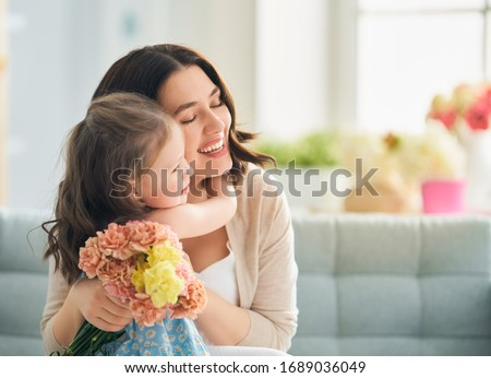 Happy mother's day! Child daughter congratulates mom and gives her flowers. Mum and girl smiling and hugging. Family holiday and togetherness.