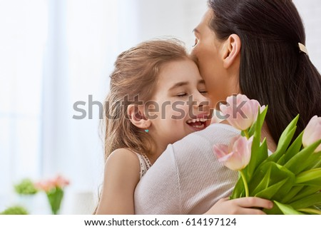 Happy mother's day! Child daughter congratulates mom and gives her flowers tulips. Mum and girl smiling and hugging. Family holiday and togetherness. #614197124