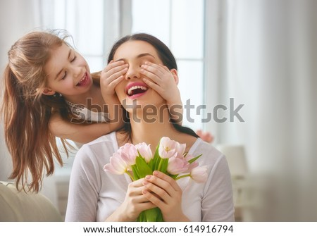 Happy mother's day! Child daughter congratulates mom and gives her flowers tulips. Mum and girl smiling and hugging. Family holiday and togetherness. #614916794