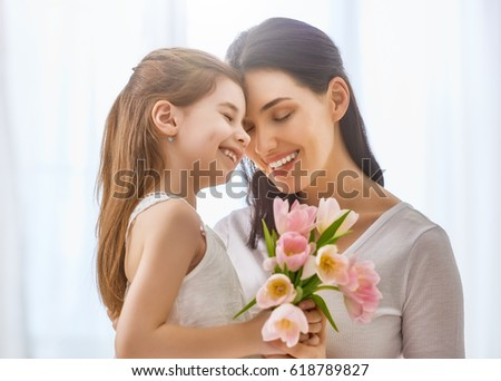 Happy mother's day! Child daughter congratulates mom and gives her flowers tulips. Mum and girl smiling and hugging. Family holiday and togetherness. #618789827