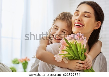 Happy mother's day! Child daughter congratulates mom and gives her flowers tulips. Mum and girl smiling and hugging. Family holiday and togetherness. #623599874
