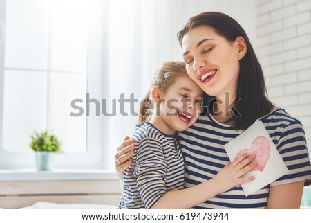 Happy mother's day! Child daughter congratulates mom and gives her postcard. Mum and girl smiling and hugging. Family holiday and togetherness. #619473944