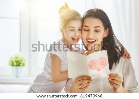 Happy mother's day! Child daughter congratulates mom and gives her postcard. Mum and girl smiling and hugging. Family holiday and togetherness. #619473968
