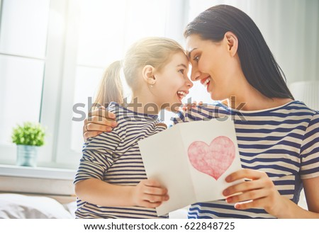 Happy mother's day! Child daughter congratulates mom and gives her postcard. Mum and girl smiling and hugging. Family holiday and togetherness.