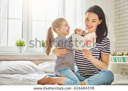 Happy mother's day! Child daughter congratulates mom and gives her postcard. Mum and girl smiling and hugging. Family holiday and togetherness. #626684198