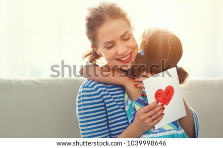 Happy mother's day! Child daughter congratulates moms and gives her a postcard   #1039998646
