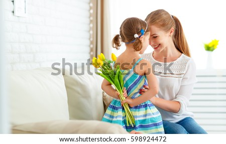 Happy mother's day! Child daughter congratulates moms and gives her a postcard and flowers tulips\r