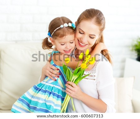 Happy mother's day! Child daughter congratulates moms and gives her a postcard and flowers tulips
