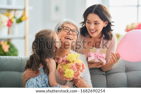 Happy mother's day! Child daughter is congratulating mom and granny giving them flowers and gift. Grandma, mum and girl smiling and hugging. Family holiday and togetherness.