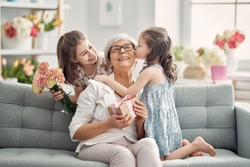 Happy mother's day! Children daughters are congratulating granny giving her flowers and gift. Grandma and girls smiling and hugging. Family holiday and togetherness.