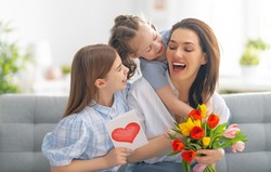 Happy mother's day! Children daughters are congratulating mom and giving her postcard and flowers. Mum and girls smiling and hugging. Family holiday and togetherness.