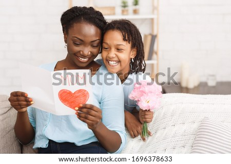 Happy Mother's Day Concept. Black child greeting her mom with flowers and card, copyspace