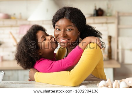 Happy Mother's Day Concept. Cute Little Black Girl Kissing And Embracing Her Happy Mom In Kitchen While They Cooking Together, Loving African Child Enjoying Spending Time With Mommy, Closeup