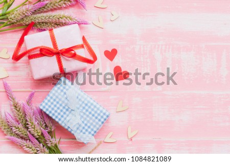 Happy mother's day concept. Top view of gift box with flower and tag with Love you MOM text on wooden block with pink handmade heart on on pastel color bright pink and white wooden background. #1084821089