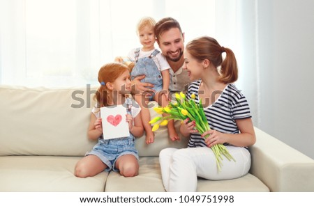 happy mother\'s day! father and children congratulate mother on holiday and give flowers