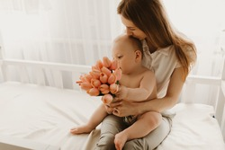 Happy Mother's Day, Happy mom with baby, congratulate mom on the holiday and give flowers