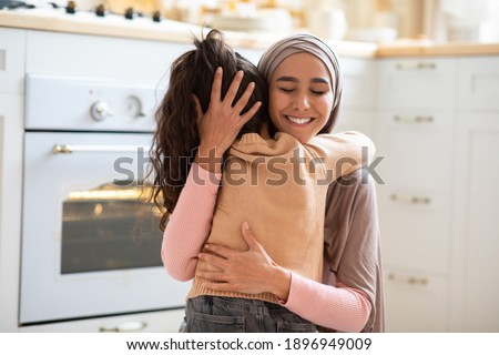 Happy Mother's Day. Little Girl Cuddling Tight Her Muslim Mom In Kitchen At Home, Expressing Love And Affection. Positive Islamic Woman In Hijab Hugging Her Child And Smiling, Closeup With Copy Space