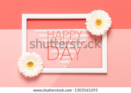 Happy Mother's Day Living Coral Pantone Color Background. Flat lay mock up greeting card with beautiful gerbera flowers and picture frame.