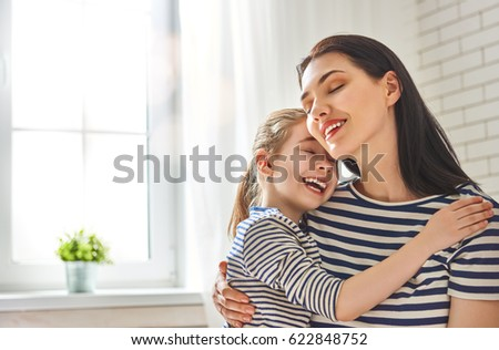 Happy mother's day! Mom and her daughter child girl are playing, smiling and hugging. Family holiday and togetherness. #622848752