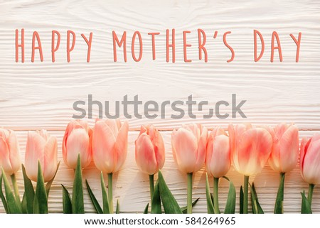 happy mother's day text sign on pink tulips on white rustic wooden background. greeting card concept. sensual tender women image. spring flowers flat lay #584264965