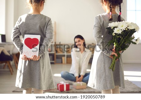 Happy Mother's Day. Two little girls holding handmade greeting card and bouquet of fresh flowers for mom. Children wishing mommy happiness and hiding gifts they have prepared as surprise behind backs