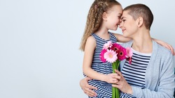 Happy Mother's Day, Women's day or Birthday background. Cute little girl giving mom bouquet of pink gerbera daisies. Loving mother and daughter smiling and hugging.