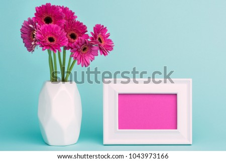 Happy Mother's Day, Women's Day, Valentine's Day or Birthday Pastel Candy Blue Coloured Background. Dark pink gerberas in a vase on a table with empty picture frame greeting card.