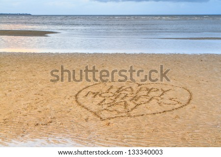 Happy Mother's Day written in a love heart, in the sand on a flat rippled beach. A calm blue sea fills the background.