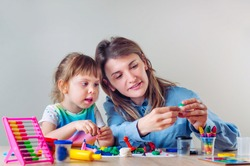 Happy mother showing her four years old daughter how to molding from child's play clay on the table. Home activities for family.