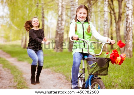 happy mother teaches his daughter to ride a bike. A mother is glad to successes of daughter #450982600