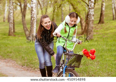 happy mother teaches his daughter to ride a bike in the park. Parents teach their children . #450954898