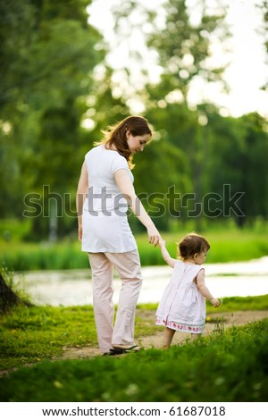 Happy mother walking with daughter in park outdoors