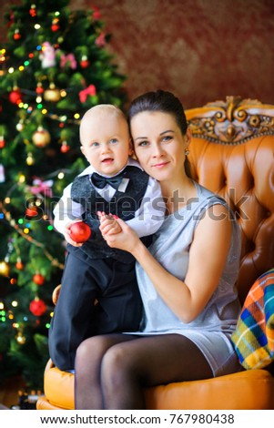 happy mother with a cheerful baby near a festive christmas tree 767980438