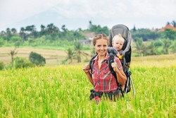 Happy mother with baby boy in carrying backpack trekking on green rice terraces. Traveling with child, active and healthy lifestyle during family summer vacation with son on  tropical island Bali