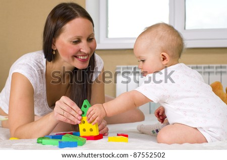 happy mother with baby playing toys