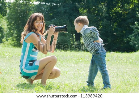 Happy mother with boy taking photo on grass in park